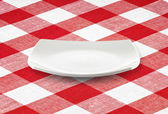 White square empty plate on red gingham tablecloth — Stock Photo