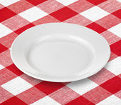 White empty plate on red gingham tablecloth — Stock Photo