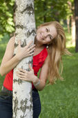 Portrait of the girl in a red blouse which smiles and embraces a birch. — Stock Photo