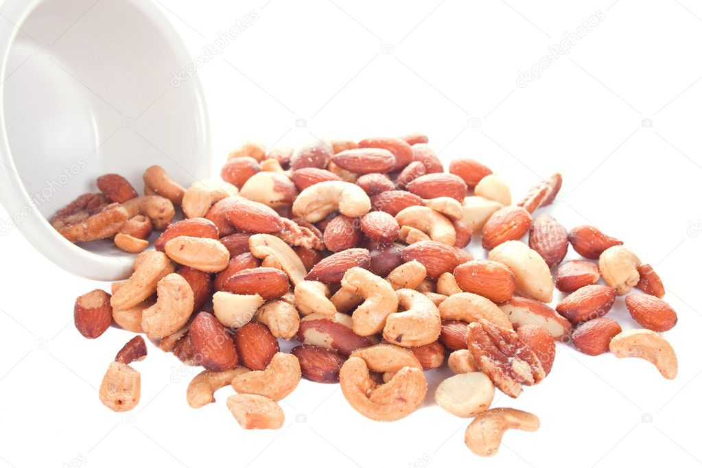 Mixed nuts spilling out of a white ramekin — Stock Photo #7313919