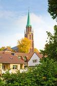 高耸于房子的砖教会 — 图库照片