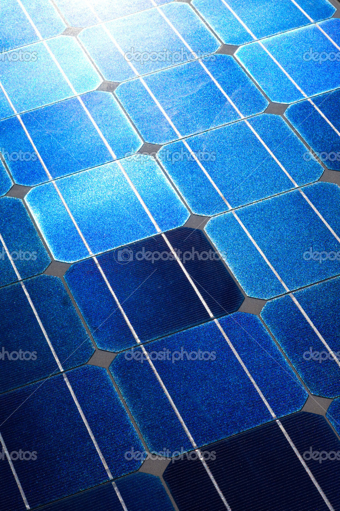 Pattern of solar cell wafers in photovoltaic solar panel with sun glare.  Stock Photo #6822133