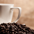 Coffee beans ad cup on yellow. focus on foreground — Stock Photo