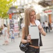 Stock Photo: Young Business Womwith tablet computer walking in public spac