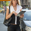 Young Woman with tablet computer walking on urban street — Stock Photo