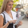 Woman with iPad tablet computer walking on urban street — Stock Photo #7522659