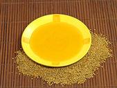 Honung i gul tallrik och blomma pollen. — Stockfoto