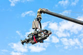 Tv camera on a crane against blue sky — Stock Photo
