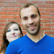 Stock Photo: Couple in love smiling with red brick wall