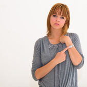 Young woman checking the time on her wrist watch — Stock Photo