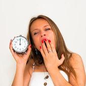 Yawn-beautiful young woman holding alarm clock — Stock Photo