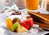 Breakfast with orange juice and fresh fruits — Stock Photo