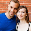Stock Photo: Young couple in love smiling with red brick wall