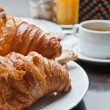 Breakfast with coffee and croissants in a basket on table — Stock Photo #6916046
