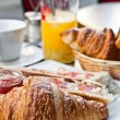 Breakfast with coffee and croissants in basket on table — Stock Photo #6917035