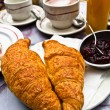 Breakfast with coffee and croissants in a basket on table — Stock Photo #6917144