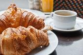 Frukost med kaffe och croissanter i en korg på bord — Stockfoto