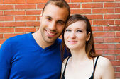 Young couple in love smiling with red brick wall — Stock Photo