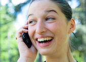 Outdoor portrait young woman talk on a cellular telephone — Stock Photo