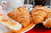Breakfast with coffee and croissants in a basket on table — Stock Photo
