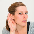 Relying on hand-ear listening young woman — Stock Photo