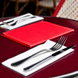 Place setting - plate, knife and fork on table — Stock Photo #6993313