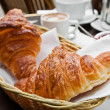 Breakfast with coffee and croissants in a basket on table — Stock Photo #7119346