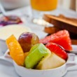 Breakfast with orange juice and fresh fruits on table — Stock Photo