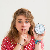 Beautiful young woman holding alarm clock and hushing — Stock Photo