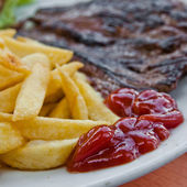 Juicy steak beef meat with tomato and french fries — Stockfoto
