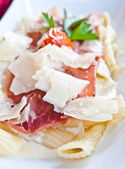 Tasty pasta with roast ham on the table — Stockfoto