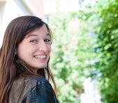 Mujer sonriendo mientras mirando hacia atrás — Foto de Stock