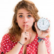 Stock Photo: Holding alarm clock and hushing
