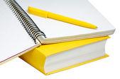 Closeup shot of yellow book, copybook and pen — Stock Photo
