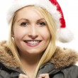 Beautiful laughing blonde woman in a parka wearing santa's hat — Stock Photo