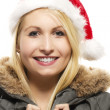 Stock Photo: Beautiful laughing blonde woman in a parka wearing santa's hat