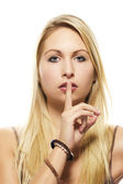 Beautiful blonde woman holding finger at her mouth — Stock Photo