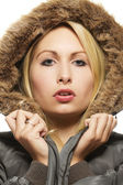 Beautiful blonde woman wearing a parka with fur — Stock Photo