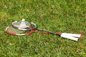 Two badminton rackets and shuttlecock on the grass — Stock Photo