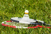 Badminton rackets and shuttlecock on the grass — Stock Photo