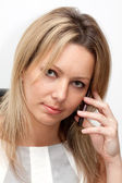 Portrait of blonde woman in white blouse with mobile phone — Stock Photo