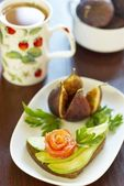 Sandwich with avocado and salmon, figs and tea — Stock Photo