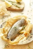 Baked trout in parchment stuffed with lemon and rosemary — Stock Photo