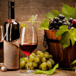 Still life with wine bottles, glasses and grapes — Stock Photo