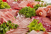 Cutting sausage and cured meat with a parsley — Stock Photo