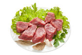 Pieces of raw meat on a white plate is isolated on a white backg — Stock Photo