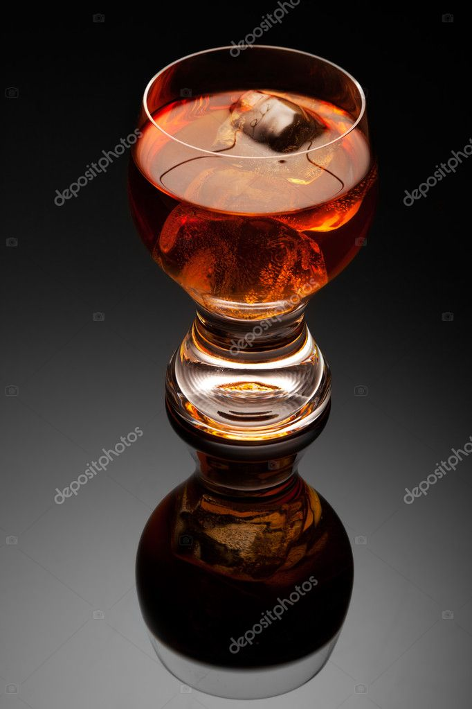 An elegant transparent glass of cognac with an ice cube in it. — Stock Photo #7377915