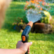 Watering the grass and flowers — Stock Photo