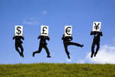 Businessman jumping and holding 4 different currency signs. dollar, pond, — Stock Photo