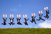 Happy businessman holding success text and jumping on the green field — Stock Photo